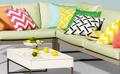 Light green outdoor sitting couch with vibrantly pattern cushions and cream, square outdoor table