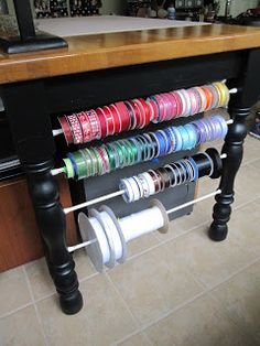 Tension Rods between table leg space to organize ribbon spools.  Add a tape measure, ruler or yardstick to the table's edge to instantly cut measured ribbon ♥