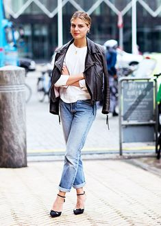 A white blouse is paired with a draped leather jacket, cuffed jeans, and ankle-strap heels