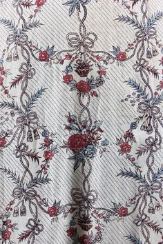 * A printed cotton 'Indienne' robe, French, the fabric 1770s, block printed cotton with vertical bands of baskets of fruits, roses and ribbons in shades of red, blue and brown,