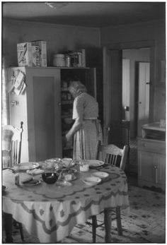 Grandmother by kitchen cabinet; table with dishes in foreground.. From Duke Digital Collections. Collection: William Gedney Photographs and Writings. Mark: Stamp. Date of print: Unknown.