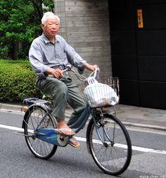 Senior gentleman riding a bike in Japan.