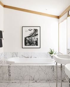 White marble bathtub in bright bathroom with black-and-white art