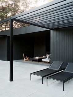 CD Poolhouse is a simple yet elegant space designed by Belgian designer Marc Merckx. The structure's defining feature is its sleek, dark façade. Stretches of straight timber merge with black-framed glass and a metal trellis. The darkened wood continues throughout the interior, along with light gray walls and concrete details.