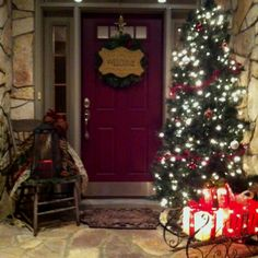 Festive front door!! Tall thin tree with wrought iron sleigh filled with light up presents! Also, lantern on left decorated with large rusty bells! Loved the look!