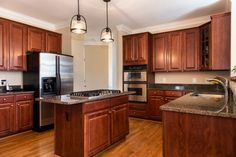 Wood cabinets with lighter tone wood floors.