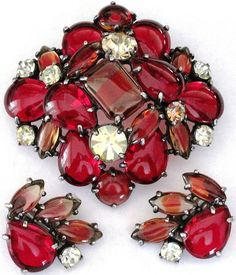"This amazing vintage pin and clip earring set are silver tone wtih watermelon yellow rhinestones, red and givre red striped glass cabochons. The pin is 2 3/4"". All pieces are signed and in excellent condition!"
