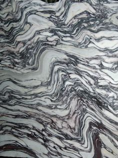 Limestone breccia, deformed so that original clasts have been flattened and stretched, and subsequently folded. Polished slab in stone merchant's yard.  Cornwall