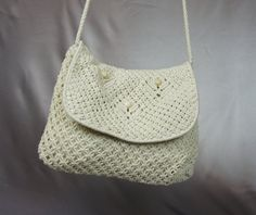 This is a woven macrame purse. It was handmade in the Phillipines. It is from the 1970s. It is in mint condition. It is lined in an off white cotton