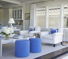 White and blue living room features white roll-arm chairs adorned with blue border pillows illuminated by polished nickel floor lamp across from white coffee table as well as round blue stools with silver nailhead trim atop white rug layered over espresso wood floors.