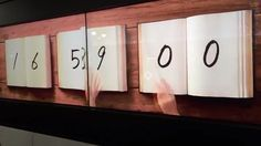 Book Clock by Masaaki Hiromura An ever-repeating video loop featuring 3 books, each representing the hours, minutes and seconds of a single day. A hand neurotically and relentlessly flips through the pages as if to remind us that time never stops moving.