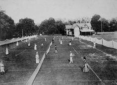 1885 Staten Island Cricket & Tennis Club This image shows the club's courts in Livingston around 1885. Arranging the players in carefully held poses,  Alice Austen, an early player, has a friend release the shutter, after she herself joins the scene. Alice is at the right of the net in the third court from the camera, wearing a dark jacket and white skirt -- and watching intently to see that her friend takes the photograph properly.
