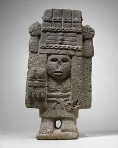 Among the many female deities worshipped by the Aztecs, those responsible for agricultural fertility held a prominent place. This sculpture depicts Chicomecoátl (seven serpents), a goddess of sustenance, especially of edible plants and corn. She is shown standing on bare feet wearing a long skirt held in place with a belt, and holding in her right hand two maize ears. Her head and most of her body are covered by a towering quadrangular headdress adorned with twisted elements across the front…