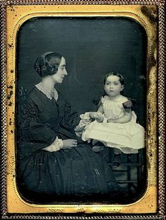 Side image of 1850's hair and neat dress on Mom and daughter.