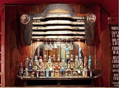 A vintage car grill doubles as a stemware rack. Ok not as a bar but a perfect headboard.