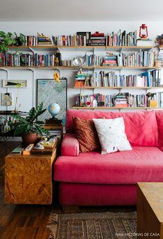 Sala de estar ampla tem sofá vermelho, plantas e prateleiras de madeira instaladas com mão francesa.