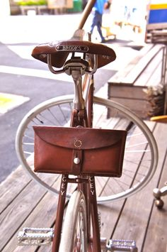 brown leather brooks bicycle saddle, matching brown leather bike clutch.
