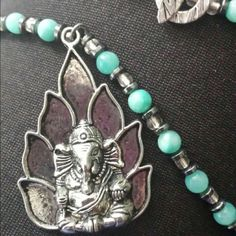 Handcrafted beaded necklace with Ganesha pendant Handcrafted by yours truly! Aqua dyed agate beads with hematite. Metal Ganesha and lotus pendant. Unique Toggle bar closure in back. Jewelry Necklaces