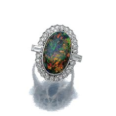 OPAL AND DIAMOND RING. The oval black opal bordered by brilliant-cut and baguette diamonds, mounted in platinum