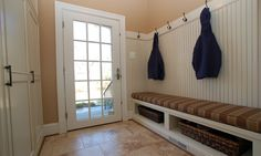 This mud room entry has a built-in bench with storage cubbies for shoes, simple wanes-coating and coat hooks