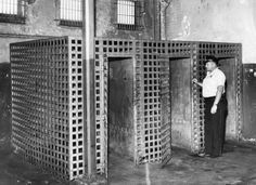 """A Joliet police officers inspects iron isolation cells, which were used to confine """"wild"""" Joliet Correctional Center inmates. Photo taken in July 1959"""