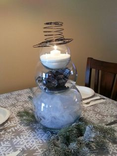 I used this interpretation of a snowman for the centerpiece on my Christmas dinner table. White and silver sparkly tulle is in the bottom bowl. It's a little hard to see, but I painted stones black to look like coal and added some scarf looking material in the middle bowl. In the top bowl, I used epsom salt and a candle. The top hat is made from black decorative wire I found in the floral section.