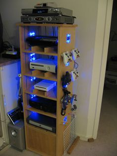 Ultimate DIY Gaming Cabinet with lighted cpu fans built in on both sides for each console and Peg hangers for controllers.