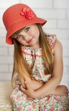 A young lady with a bright orange hat with a beautiful summery dress