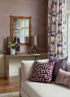 In a living room designed by Andrea Schumacher, Romo's Black Edition Cromatico drapery fabric in violet mingles with lavender grasscloth wallpaper from Kneedler Fauchère and throw pillows in various fabrics. Photo by Emily Minton Redfield