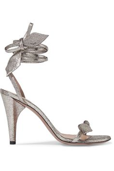 """Chloe's 'Mike' sandals are made from shimmering gunmetal cracked-leather that subtly reveals a black background - an effect the house says adds """"a touch of rock and roll."""" This pair has delicate straps that elegantly wrap around the ankle and tie into a playful bow. Wear yours with everything from cocktail dresses to jeans."""