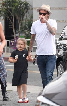 Daddy's girl: Following in her father's sporty footsteps, Harper wore a casual Nike hooded dress and sliders