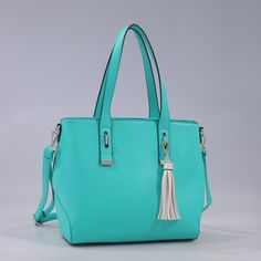 Features: Gold tone hardware Stylish contrast color tassel Double top handles Back pocket with zipper closure