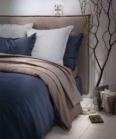 Déco naturelle en toute simplicité avec tête de lit matelassé et une branche d'arbre.