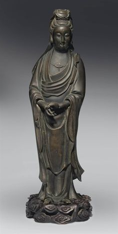 A SILVER-INLAID BRONZE FIGURE OF GUANYIN -  19TH CENTURY.