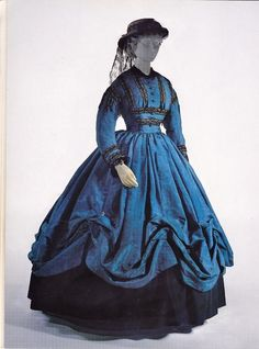 American walking dress, c. 1864, of blue watered silk, trimmed with black lace, white ribbon, and jet beads. metal rings sewn into the seams are designed to be used with a skirt lifting device to raise the skirt into swags over an underskirt. Photo copyright of The Met,