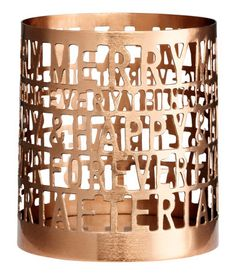 Tea light holder in metal with cut-out text. Diameter 3 1/4 in., height 3 1/2 in.