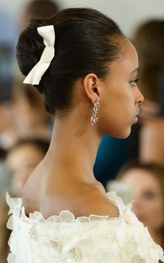 Oscar de la Renta Bridal Spring 2016: Ribbons aren't just for little girls anymore. The gorgeous updos at Oscar de la Renta were complemented by ivory bows.