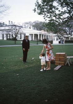 President John F. Kennedy, First Lady Jacqueline Kennedy, and John F. Kennedy, Jnr. ~ White House, 1962From Jackie's bare feet to the makeshift seesaw, there's something really natural about this pic of the parents and their son… it was usual for The President to randomly turn up and check-in on the children's playtime, as he does so here. And then its as if he's proudly standing back to properly enjoy the maternal scene of his son drinking some juice from the hand of his wife.