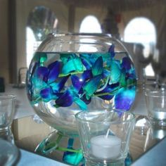 I love the colors!  My centerpieces! Blue orchids in a fish bowl. I'll probably add blue marbles to the bottle of the bowl though for more color another pinner said but I love the turquoise in them so would like to add the turquoise glass stones in the bottoms :)