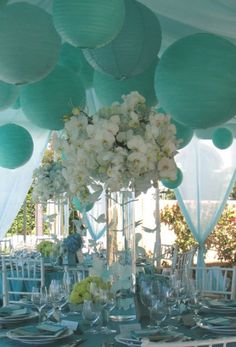 Mint and turquoise lanterns supply some color pizzazz to wonderful white centerpieces.