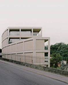 The design of its concrete street facade follows the curved topography of the road and was informed by largely blank walls found in Romanesque architecture and at the Pisa Baptistery. It is made up of pitched, bush-hammered panels that are slotted within a gridded exoskeleton and punctuated only by the small entrance. Small Entrance, Romanesque Architecture, Concrete Wall, Dezeen, Blank Walls, Facade, Garage Doors, Minimalist, Exterior