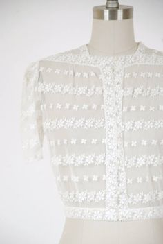 Vintage late 1930s blouse in a transparent white silk mesh, with row after row of floral stripes. The cut is perfect - cropped just to the waist with a fitted waistband, slightly puffed sleeves. A bold row of daisies runs from the shoulders, to become the button placket and then waistband. Pair this over a saucy darker slip. Its bound to be a favorite. ✂-----Measurements  Bust: 41 Waist: 28 Length: 17.5  Label: None Present Material: Silk Condition: Good plus  This blouse is clean and ready…