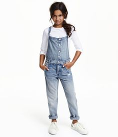 Loose-fit bib overalls in soft, washed denim with distressed details. Narrow, adjustable suspenders, buttons at front, and tapered legs. Side pockets, coin pocket, and back pockets.
