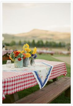 there is something so lovely and simple about a picnic table, a red checked tablecloth and flowers in old containers...