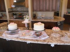 Two cakes, one with Booties, one with Roses, Cupcakes, Candy's and Mixed Nuts, on the bar opposite side of the sink counter...