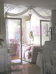 "wow how pretty.... love how the room is ""split"" by that entryway...perhaps it's a bedroom and a sitting room? Love the filigree piping in the corners swooped by some white sheer and then open style doors..... wow... and of course, the wood floors make the whole look"