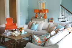 The homeowner's favorite hues inspired this living room, expressly designed to make people smile. Pale aqua walls encourage relaxation while bold orange accents are energizing, resulting in a yin and yang that's ideal for the creative, color-loving homeowner. The beige sectional offers ample seating for guests.