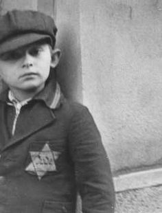 A Jewish boy wearing the compulsory Star of David. Prague, between September 1941 and December 1944.