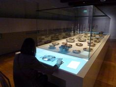 The Maritime Museum, Amsterdam: Interactive projection surface adding context to artifacts. A way to pair objects and interpretation. Boots in case and interactive selection of Beat Cop stories on surface in front?