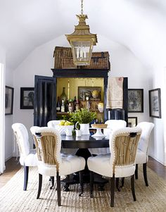Dining room, white walls & upholstery, with black armoire and table. Designer Dan Marty, Photo Victoria Pearson. House Beautiful magazine.